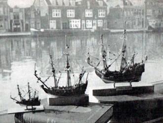 """Drie historische modellen gefotografeerd in 'n historischdécor: het Spaarne met op de achtergrond enkele van de vele mooie oude geveltjes van Haarlem. Van links naar rechts een ongeveer 10 cm lang model (van scheg tot spiegel) van het fluitschip de """"Sullevere Halve Maen"""" omstreeks 1635; daarnaast'n blok-model van de """"Rôo Draeck"""" (de scheg van dit model is niet geheel aan de maat) en tenslotte- nog eens de """"Ghulden Sonne""""."""