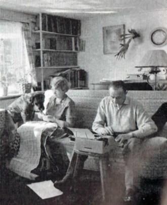 """In de gezellige woonkamer van de """"Licht-boey"""" werkt Dick Dreux aan een nieuw hoorspel, mevr. Dreux aan één van haar hobbies:smyrnawerk en """"de knaap van 'n hond"""", die uw verslaggever bijna overboord werkte ziet belangstellend toe. Achteraf bleek het toch een lief dier te zijn ..."""